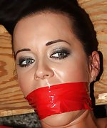 Bound to the bed, mouth-stuffed, tape-gagged